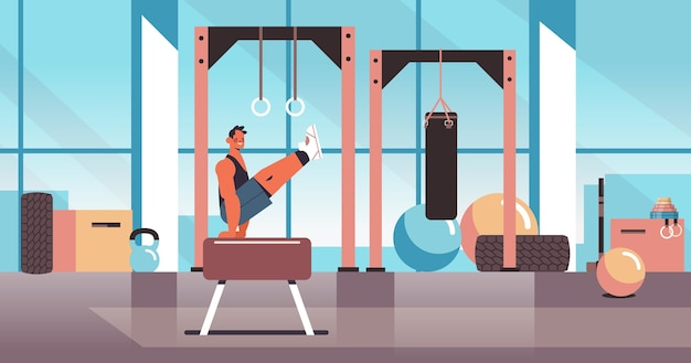Professional gymnast doing physical exercises on pommel horse working out fitness training healthy lifestyle concept modern gym studio interior