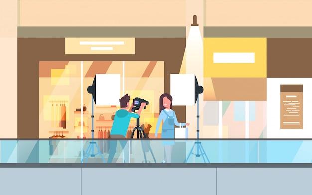 Professional man photographer using dslr camera on tripod shooting beautiful woman model girl posing in modern shoping mall supermarket interior horizontal full length