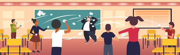 Pupils demonstrating bad behavior throwing papers mocking and teasing male teacher during lesson bullying public disapproval concept school classroom interior horizontal
