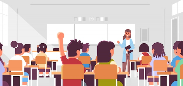Pupils group listening to female teacher schoolboy raising hand to answer in classroom during lesson teaching education concept modern class room interior