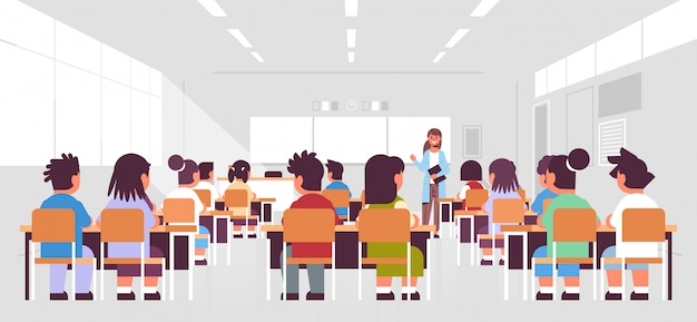 Pupils group sitting and listening to female teacher in classroom during lesson teaching education concept modern class room interior