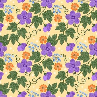 黄色の背景に緑の葉を持つ紫とオレンジ色の花。