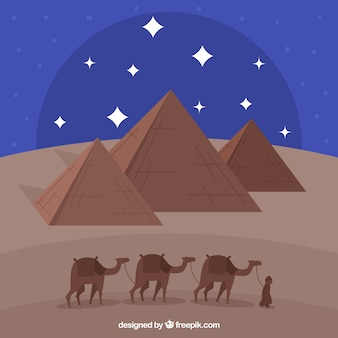 Pyramid landscape with caravan at night