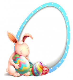 A rabbit with easter eggs beside an egg-shaped signage