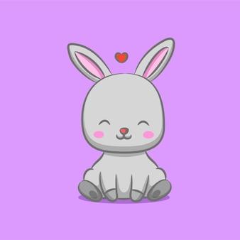 愛のサインの下に座っている長い耳を持つウサギ