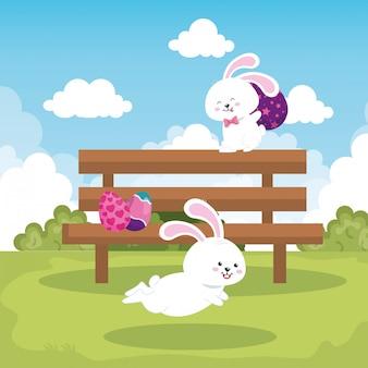 Кролики в парке сцены с пасхальными яйцами украшены дизайн векторная иллюстрация