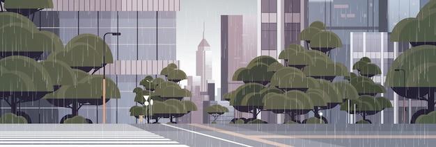 横断歩道の都市の建物のスカイライン近代建築の街並みと空の街路を雨が降っています