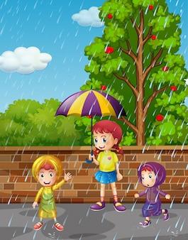 雨の中で3人の子供がいる雨季
