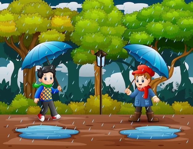 公園のイラストで傘を持っている2人の男の子と梅雨の季節