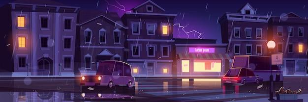 가로등 기둥과 사거리가있는 조명 도로를 따라가는 자동차가있는 밤 마을의 비오는 거리, 습한 날씨
