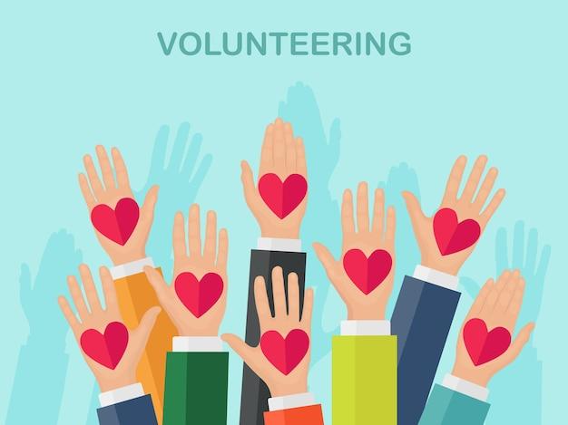 カラフルなハートで挙手。ボランティア、チャリティー、献血のコンセプト。お手入れありがとうございます。群衆の投票