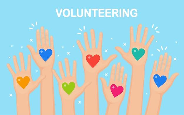 カラフルなハートで挙手。ボランティア、慈善団体、献血のコンセプト。お世話になりました。群衆の投票。