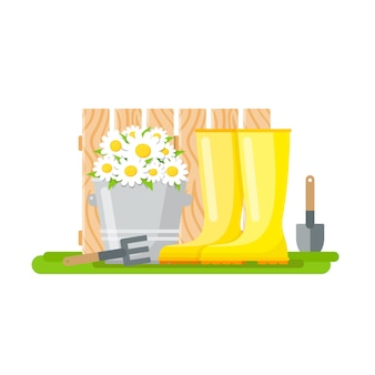 Rake, paddle, rubber boots and bucket with daisies