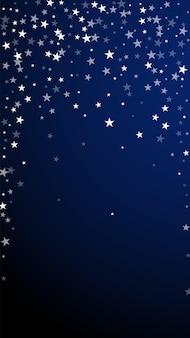 임의의 떨어지는 별 크리스마스 배경입니다. 짙은 파란색 배경에 미묘한 날아다니는 눈 조각과 별. 매혹적인 겨울 은색 눈송이 오버레이 템플릿입니다. 극적인 수직 그림입니다.