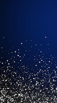 임의의 흰색 점 크리스마스 배경입니다. 짙은 파란색 배경에 미묘한 날아다니는 눈 조각과 별. 매력적인 겨울 은색 눈송이 오버레이 템플릿입니다. 압도적인 세로 일러스트.