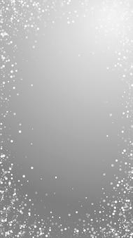 임의의 흰색 점 크리스마스 배경입니다. 회색 배경에 미묘한 비행 눈 조각과 별. 실제 겨울 은색 눈송이 오버레이 템플릿입니다. 눈에 띄는 세로 그림입니다.