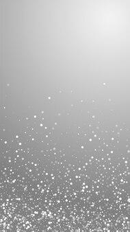 임의의 흰색 점 크리스마스 배경입니다. 회색 배경에 미묘한 비행 눈 조각과 별. 매력적인 겨울 은색 눈송이 오버레이 템플릿입니다. 완벽한 수직 그림입니다.