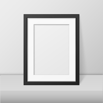 Realistic blank black picture frame closeup standing on white table. design template