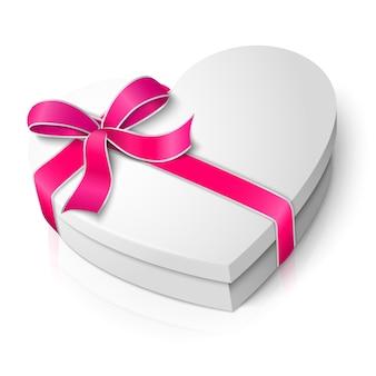 Реалистичная пустая белая коробка в форме сердца с розовой и белой лентой и бантом на белом фоне с отражением. для вашего дня святого валентина или любви представляет дизайн.
