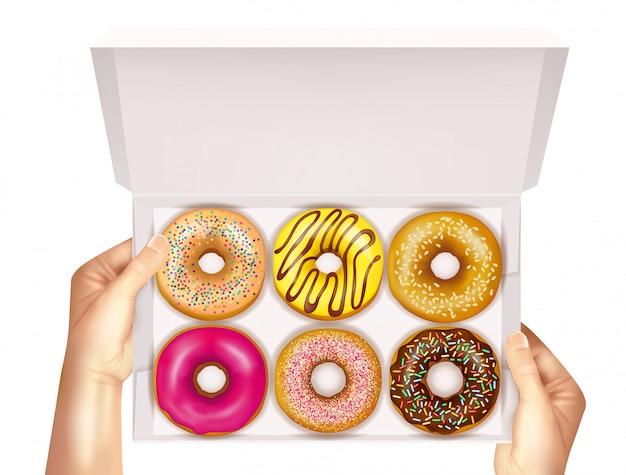 Реалистичные пончики в коробке, держащей руками