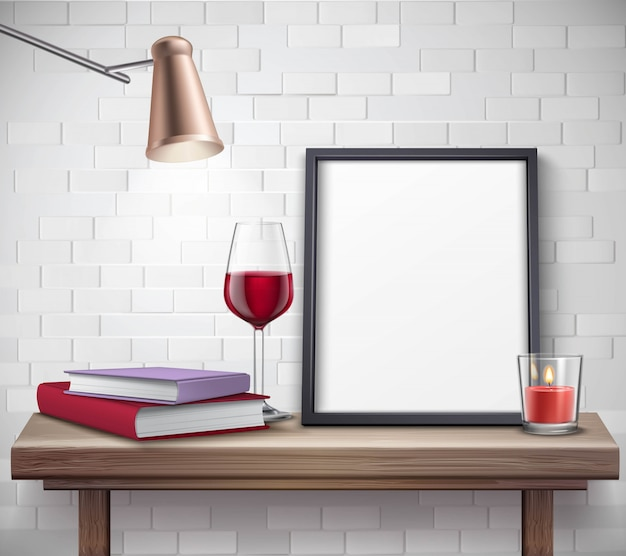 Realistic frame template on the table with glass of wine candle lamp and books