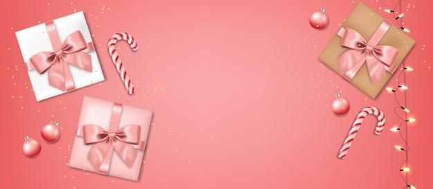 弓とボールの分離、ピンクの背景、クリスマスのお菓子とライト、メリークリスマス、お祝いの現実的なギフト