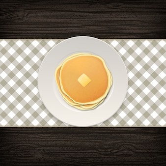 Realistic pancake with a piece of butter on a white plate closeup on wood background, top view.