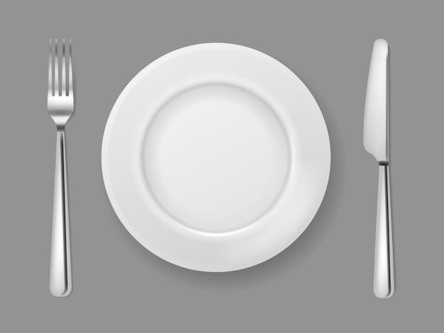 リアルなプレートナイフフォーク。銀カトラリー白い食品空プレート金属フォークとナイフのディナーテーブルトップビューの分離
