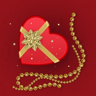 A realistic red gift box with shape of heart decorated with a gold bow, top view.