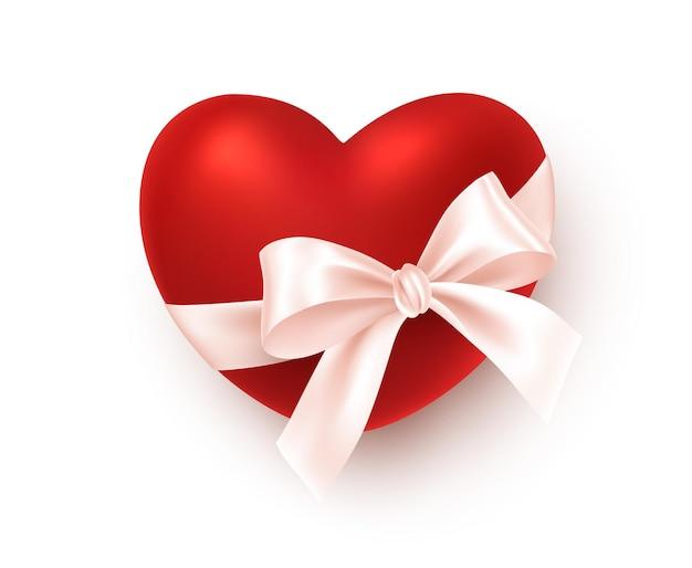 Реалистичное красное сердце с белым бантом из шелковой ленты на белом фоне.