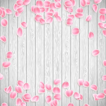 Realistic sakura petals on a white wooden background.