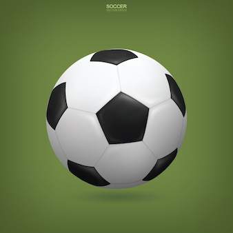 Realistic soccer ball on green background.