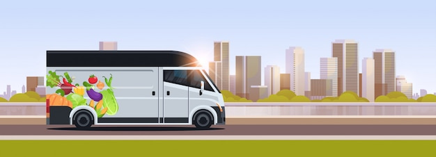 Realistic van with organic vegetables on city highway natural vegan farm food delivery service vehicle with fresh veggies cityscape background horizontal flat