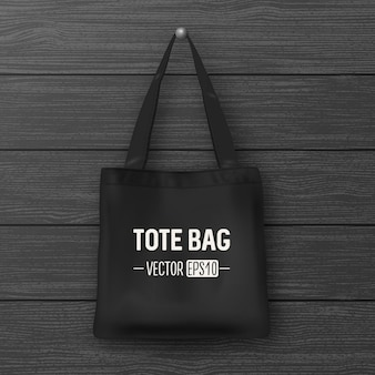 Realistic vector black empty textile tote bag. closeup on wood background. design template for branding, mockup. eps10 illustration.