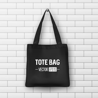 Realistic vector black textile tote bag. closeup on brick wall background. design template for branding, mockup. eps10 illustration.