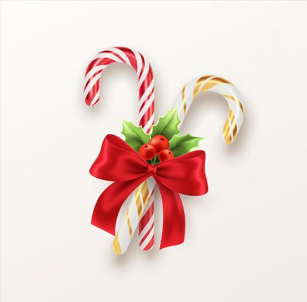 赤いリボンとクリスマスのヒイラギの小枝が付いている現実的なクリスマスキャンデー杖