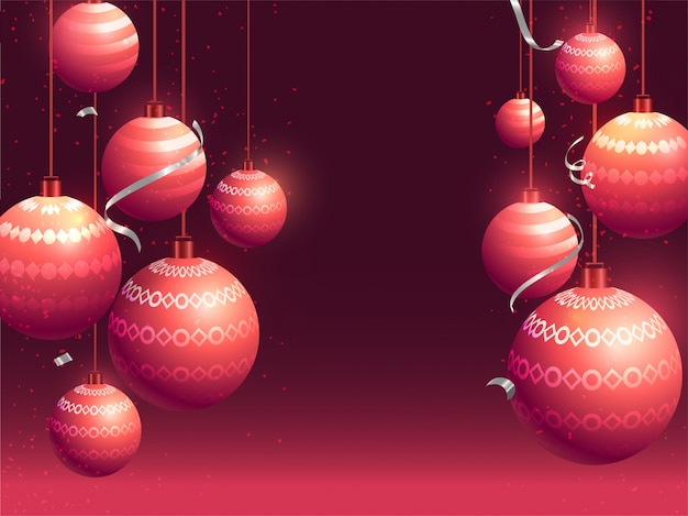 Realstic baubles hang on burgundy   greeting card .