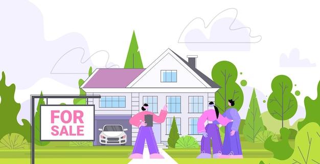 Риэлтор показывает клиентам красивый загородный дом, агентство недвижимости предлагает ипотечную ссуду горизонтально во всю длину