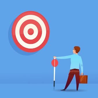 青色の背景のフラットに矢印ターゲットビジネスの成功の概念を保持しているリアビュー実業家
