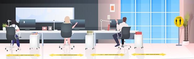 コロナウイルスの流行を防ぐために距離を置いて職場に座っているビジネスマンの背面図19保護