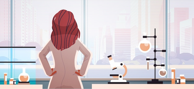 ガラス窓の薬のヘルスケアの概念を楽しみにして制服を着た女性医師の背面図
