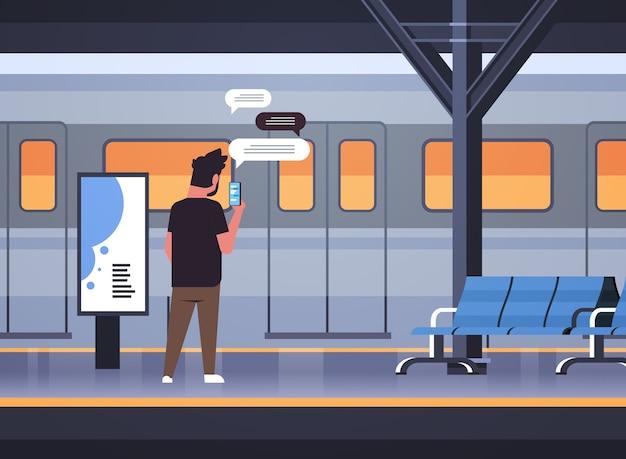Вид сзади человек, стоящий на платформе, используя мобильное приложение в чате на смартфоне, социальная сеть, чат, пузырь, концепция коммуникации, поезд, метро или железнодорожная станция, полная горизонтальная векторная иллюстрация