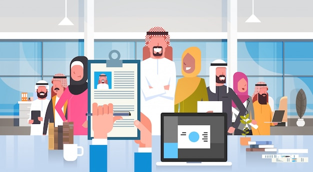 Recruitment hand holding resume choosing candidate from arab business people group in modern office human resources concept