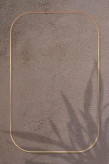 Rectangle gold frame on leaf shadowed brown background