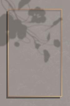 Cornice rettangolare in oro su sfondo di marmo marrone ombreggiato da foglia