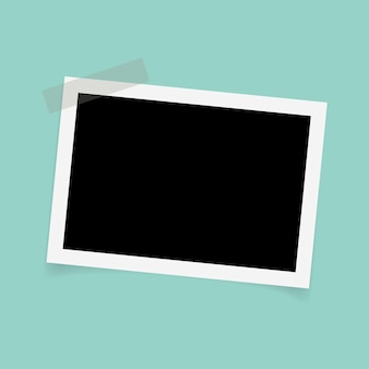 Rectangle photo frames with sticky tape on green background.