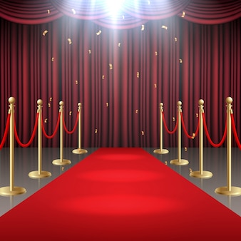 Red carpet and curtain and barrier rope in glow of spotlights