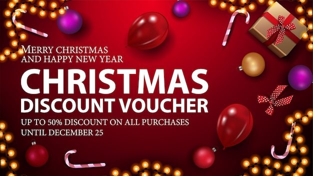 Red christmas voucher with present, candy canes, christmas balls, balloons and garland, top view