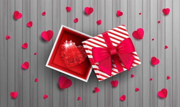 Красный бриллиант в бумажной коробке на деревянном