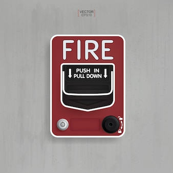 Red fire alarm switch on gray concrete background.